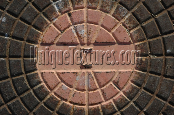 manhole pattern shadow textual weathered industrial metal multicolored orange/peach