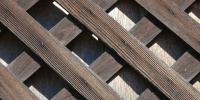 slats fence angled diamonds pattern shadow weathered architectural wood dark brown